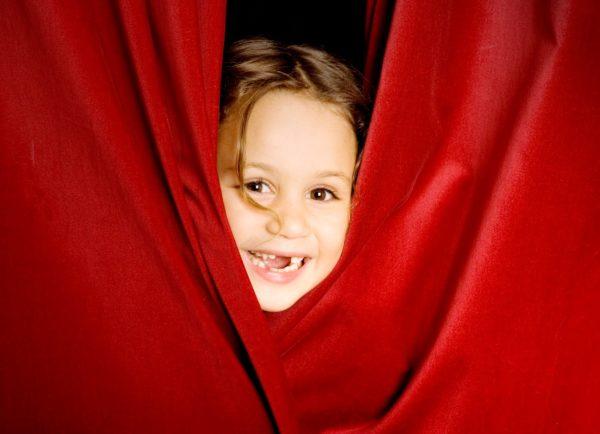 Девочка просунула голову в красный занавес и смеётся