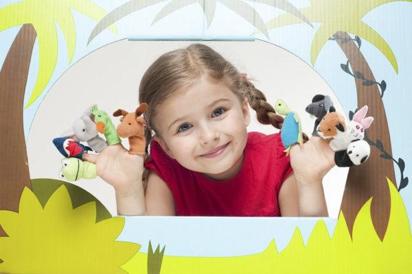 Улыбающаяся девочка с пальчиковыми куклами на руках