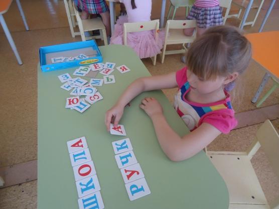 девочка выкладывает слова из букв