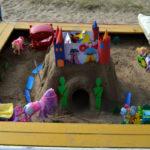 Дворец с башнями в песочнице, вокруг небольшие игрушки