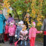 Дети, родители и воспитатели стоят на улице в осенней одежде