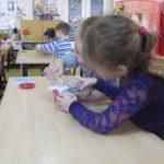 Дети, сидя за партами, очищают воду через фильтр
