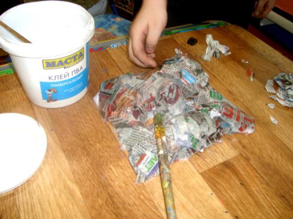 На маску нанесена газетная бумага, на столе клей и кисть
