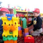 Два мальчика строят замок из напольного строительного конструктора