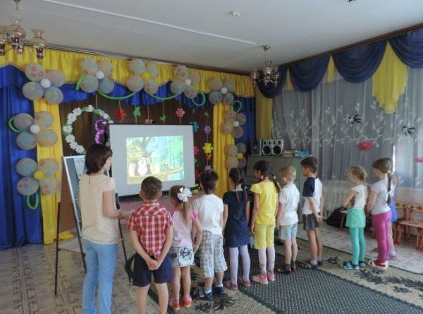 Воспитатель и дети стоят перед экраном, на котором демонстрируется мультфильм
