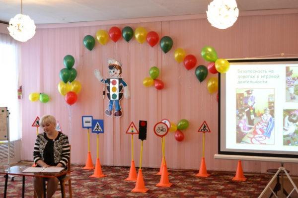 Педагог выступает в зале, на заднем плане — шарики, знаки дорожного движения и экран с презентацией