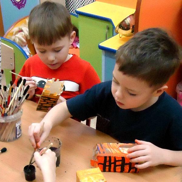 Два мальчика рисуют на раскрашенных коробочках кирпичную кладку