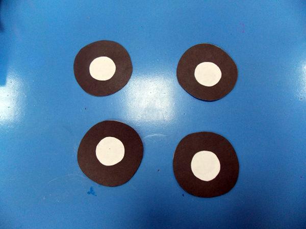 Четыре круга чёрного цвета с белой серединой — заготовки для колёс