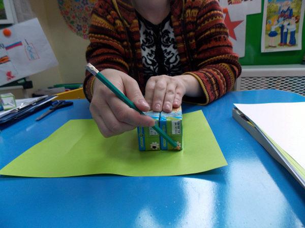 Педагог обводит на листе бумаги контуры заготовки