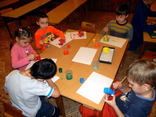 Пятеро детей за столом делают кресла из спичечных коробочек