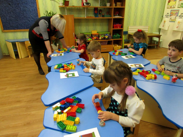 Дети за столами занимаются Лего-конструированием, воспитатель помогает