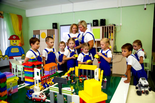 Воспитатели и дети в синих комбинезонах стоят около моделей, выполненных из конструктора