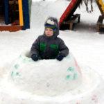 Ребёнок сидит в летающей тарелке, сделанной из снега