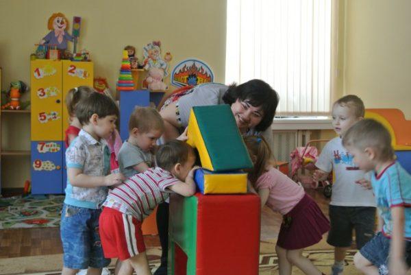 Воспитатель и дети заглядывают в домик, построенный из блоков большого конструктора