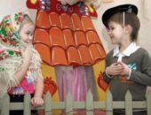 Мальчик и девочка в платке играют сценку на фоне декораций: домика и забора