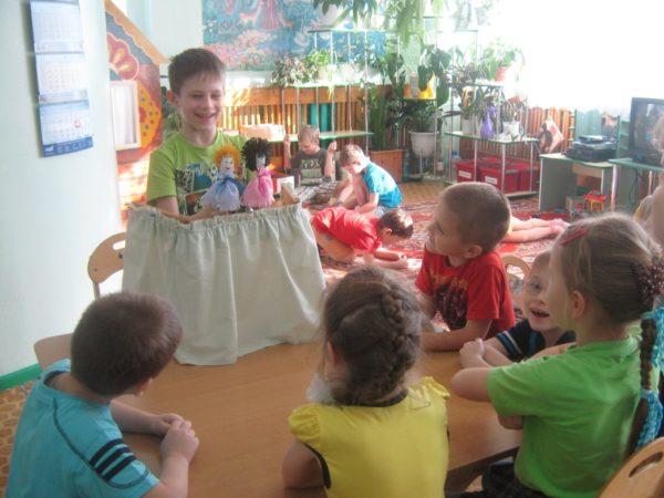 Мальчик показывает представление с куклами, дети сидят за столом и смотрят