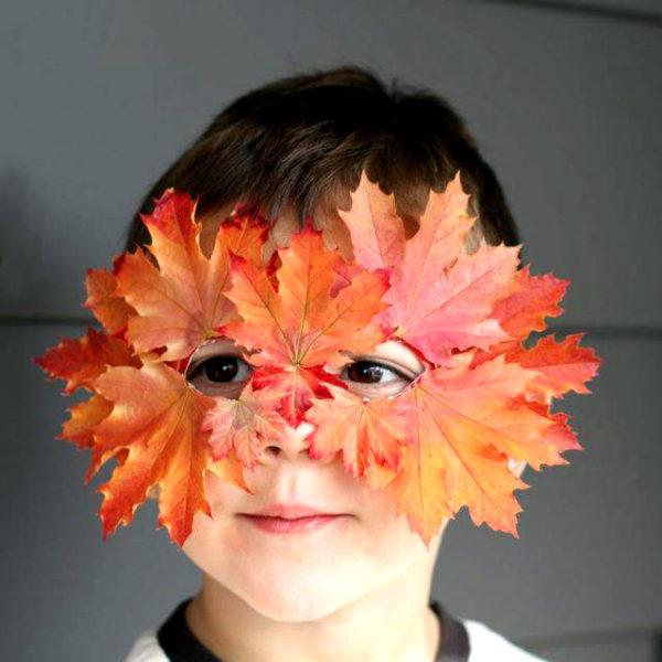 Мальчик в маске из осенних листьев