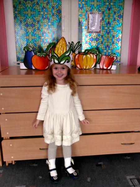 Девочка стоит с маской кукурузы на голове
