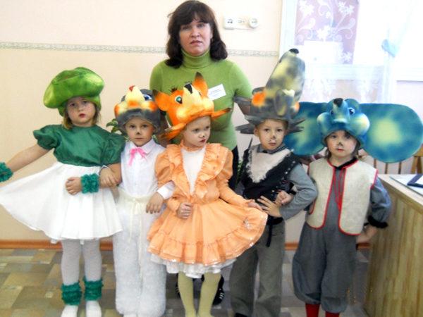 Воспитатель стоит рядом с детьми в театральных костюмах