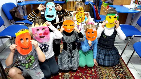 Дети в масках сидят на полу