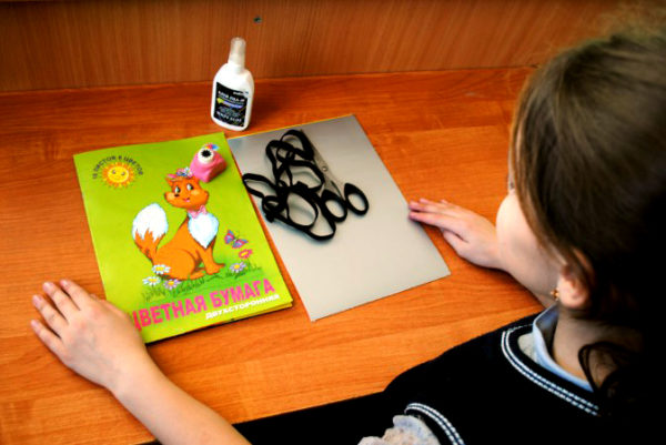 Перед девочкой на столе лежат цветная бумага, ножницы, картон, клей, резинка
