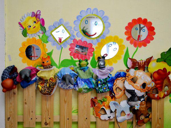 Деревянный заборчик с масками, куклами и цветами с зеркальными серединками