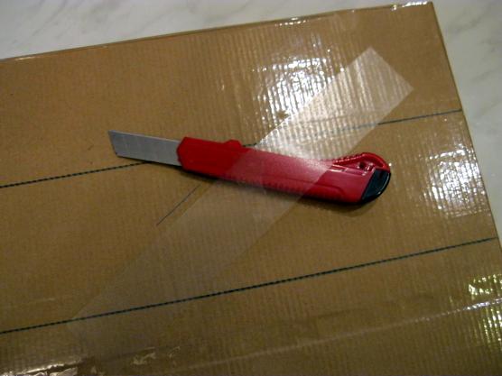 На листе картона лежат канцелярский нож и полоса прозрачного пластика