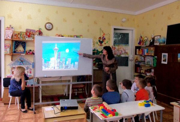 Две воспитательницы показывают детям презентацию