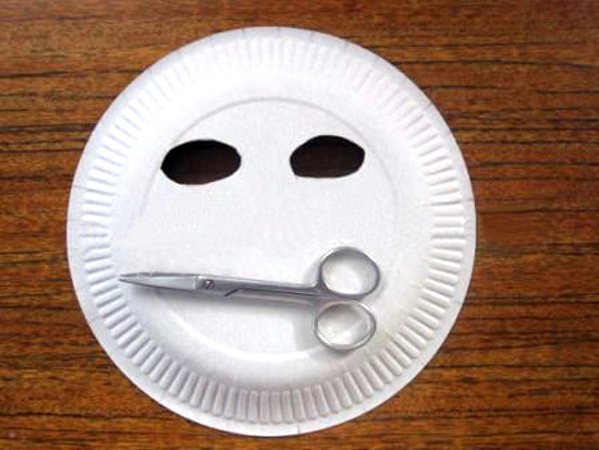 В тарелке маникюрными ножницами вырезаны отверстия для глаз