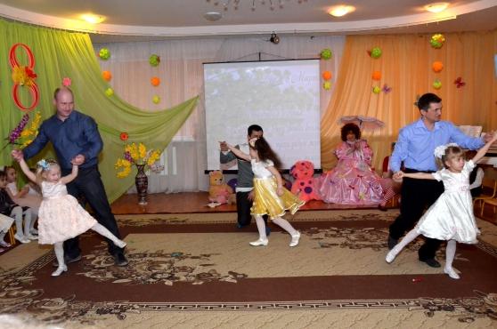 Папы танцуют с дочками на празднике, посвящённом 8 Марта