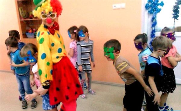 Воспитатель в костюме клоуна и дети в масках играют в подвижную игру