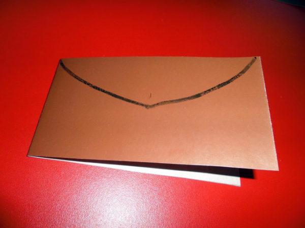 На картоне, сложенном пополам, нарисована полукруглая линия