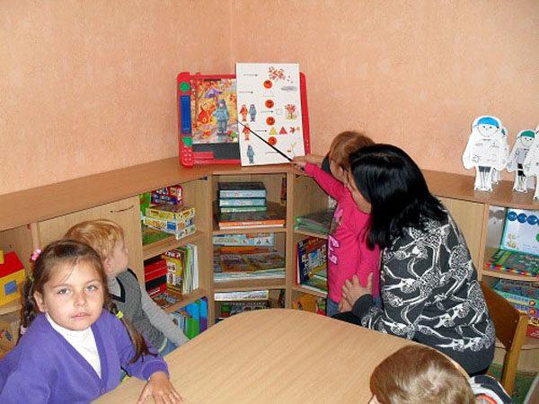 Дети и воспитатель сидят за столом, одна девочка водит указкой по картинке