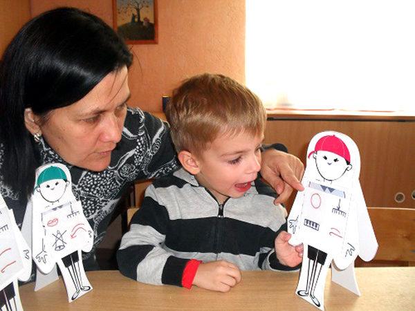 Мальчик держит в руке объёмную модель человечка и произносит звук, педагог помогает
