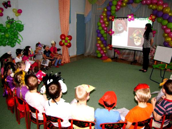 Воспитатель демонстрирует презентацию детям в костюмах