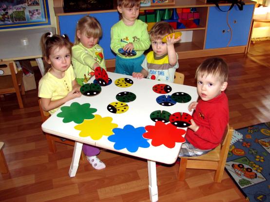 Дети сидят за столом, на котором разложены наглядные материалы разных цветов