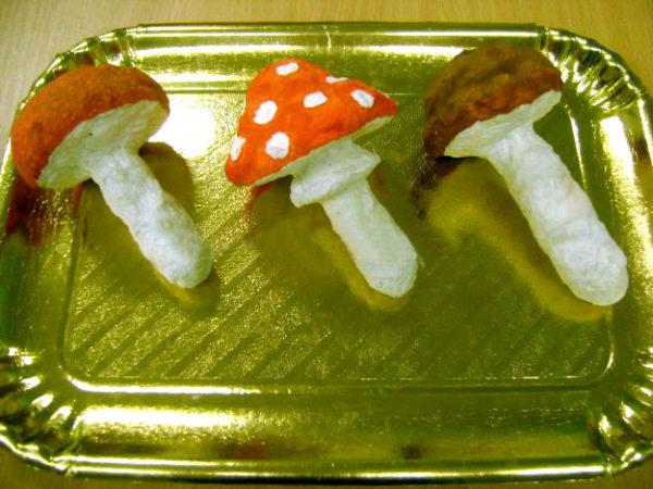 Три раскрашенных муляжа грибов лежат на подносе