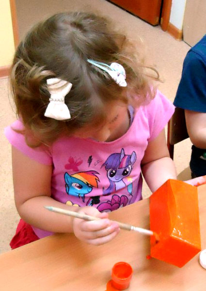 Девочка раскрашивает коробку в оранжевый цвет