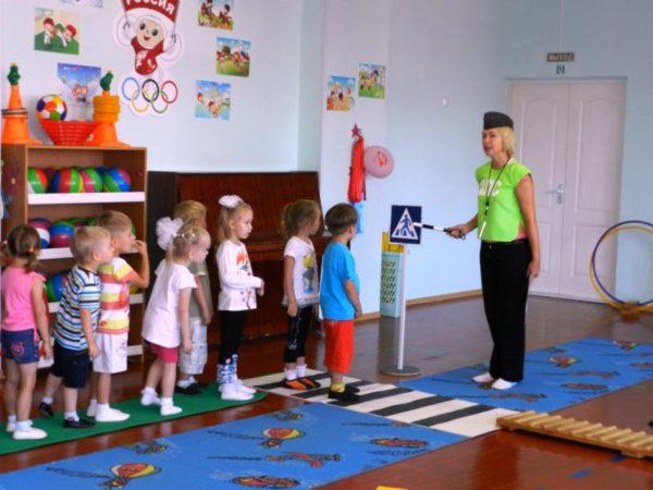 Воспитатель стоит в форме постового, дети идут шеренгой по разложенным на полу дорожкам
