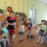 Дети и педагог играют в подвижную игру с мячом
