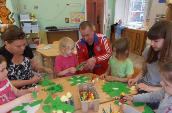 Родители с детьми делают аппликации с зелёными листьями из бумаги