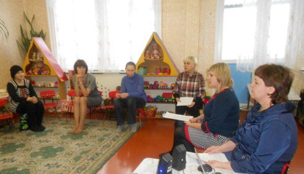 Родители сидят полукругом в просторном зале с ковром на полу