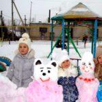 Три девочки стоят рядом с медведем и куклой, сделанными из снега
