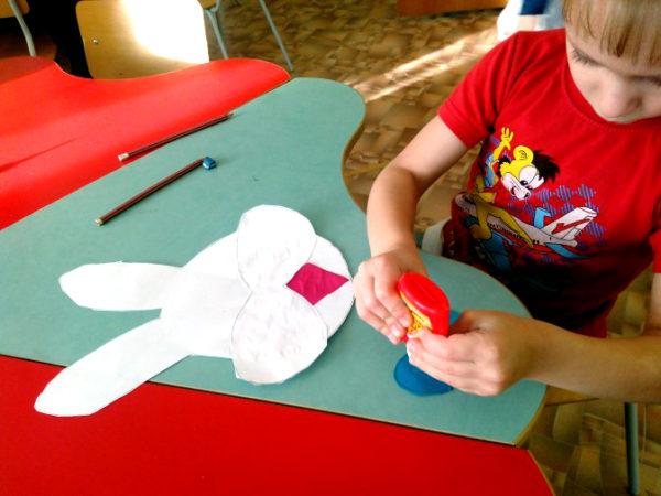 Мальчик склеивает детали маски зайчика
