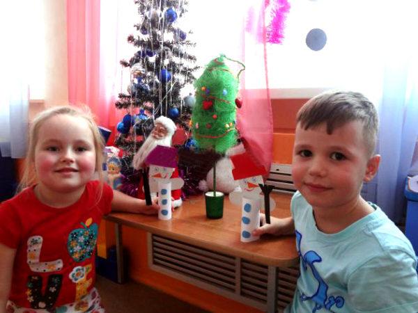 Мальчик и девочка держат снеговичков из бумаги