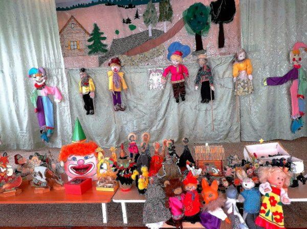 Театральный уголок с разными куклами на столах и на ширме