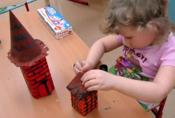 Девочка раскрашивает крышу коричневым цветом