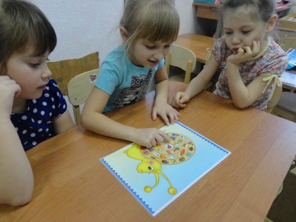 Три девочки сидят за столом и выполняют задание с буквой «Р»