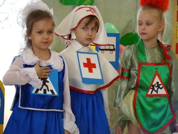 Три девочки в костюмах со знаками дорожного движения на груди участвуют в представлении