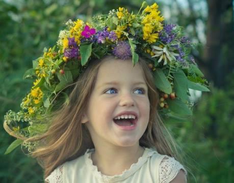 Улыбающаяся девочка в венке из цветов